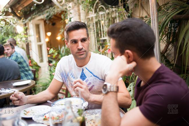 Men eating together at an outdoor cafe