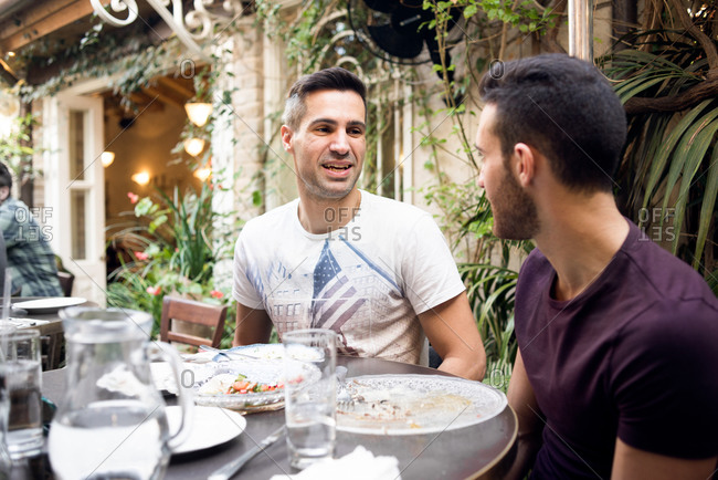 Two men having conversation at outdoor cafe