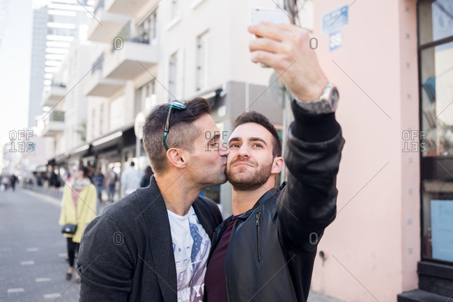 Man kisses his partner's cheek while he takes a selfie