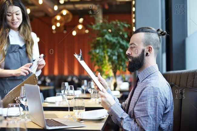Man looking at menu in a restaurant