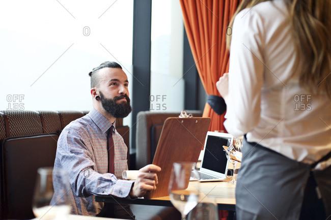Waitress taking man's order