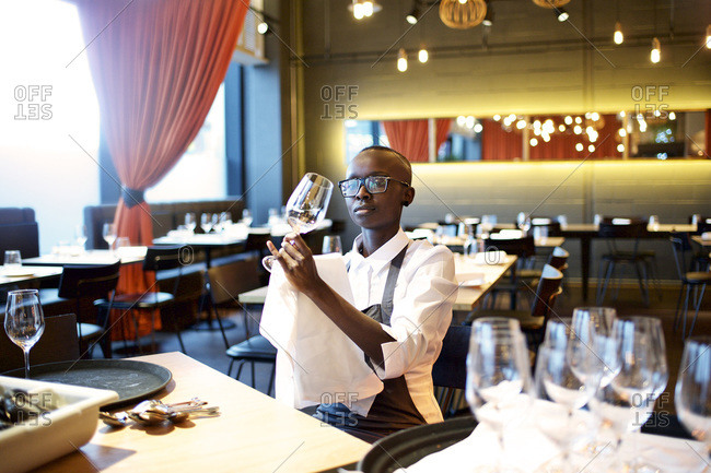 Waitress cleaning a wine glass in a restaurant