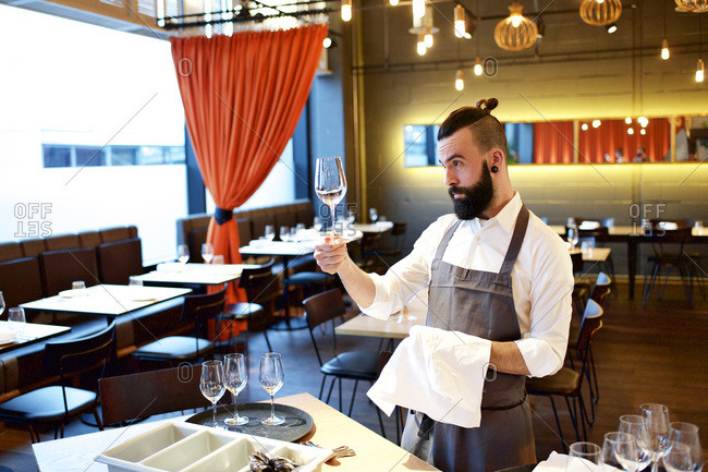 Waiter cleaning a wine glass in a restaurant