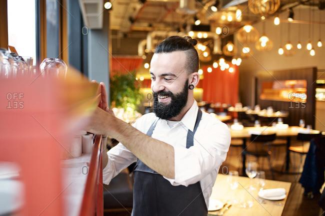 Waiter getting a roll of receipt paper from a shelf