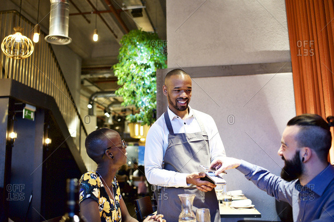 Man paying waiter for meal with his cell phone