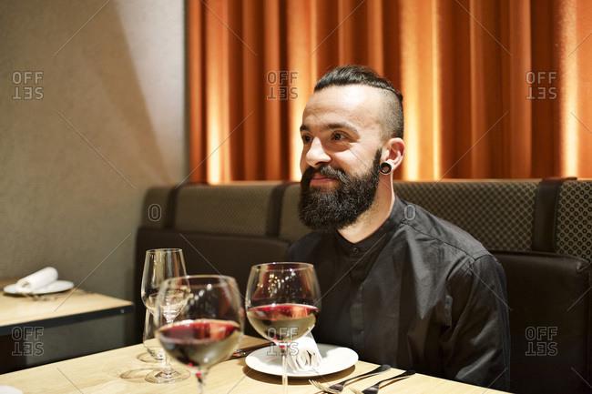 Man drinking red wine in a restaurant