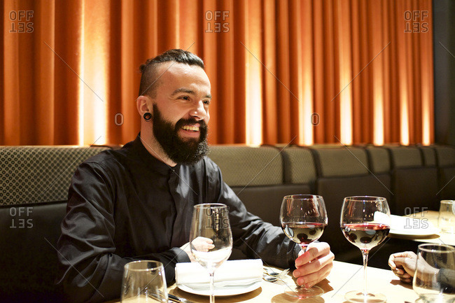 Man drinking a glass of red wine in a restaurant
