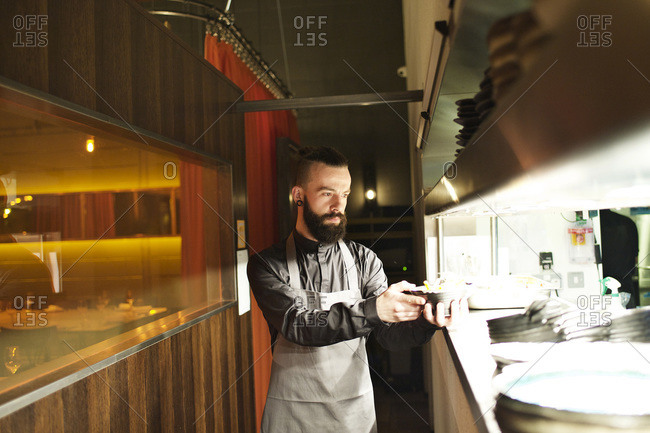 Waiter grabbing food from under a heat lamp