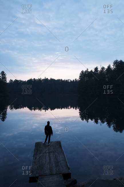 Photographer standing on a dock looking at a lake