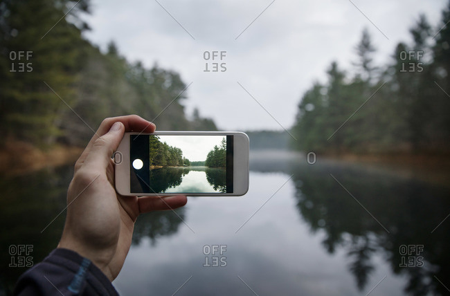 Person taking photo of a lake with a smart phone