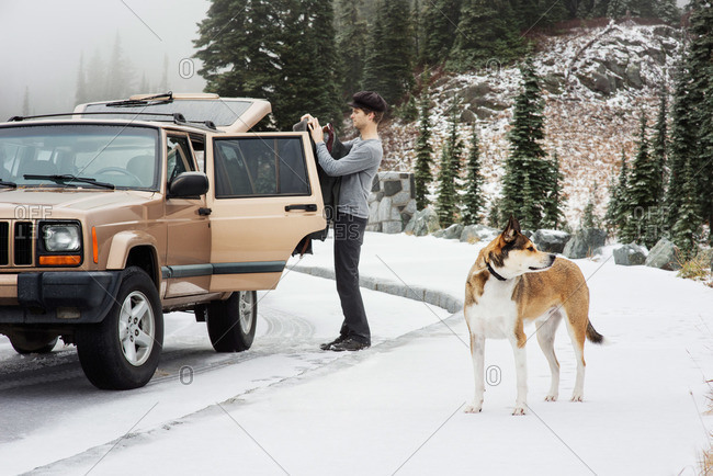 Man getting coat out of his vehicle with his large dog