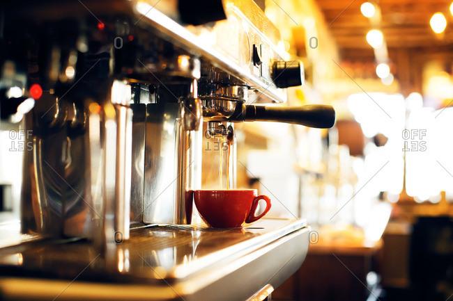 Espresso brewing into a cup