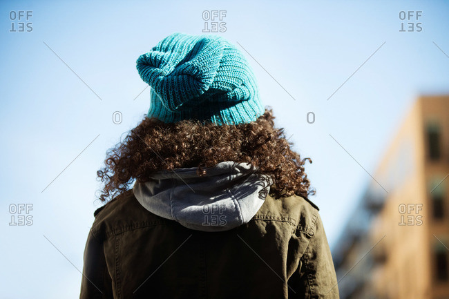 Girl with curly hair and hat from behind