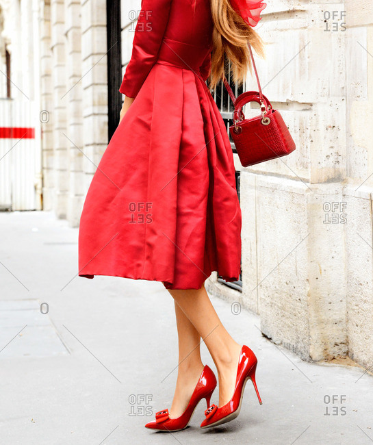 Woman in a red dress and red high heels with a handbag