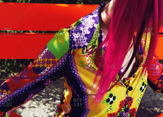 Close-up of a woman with pink hair wearing a brightly colored button down shirt