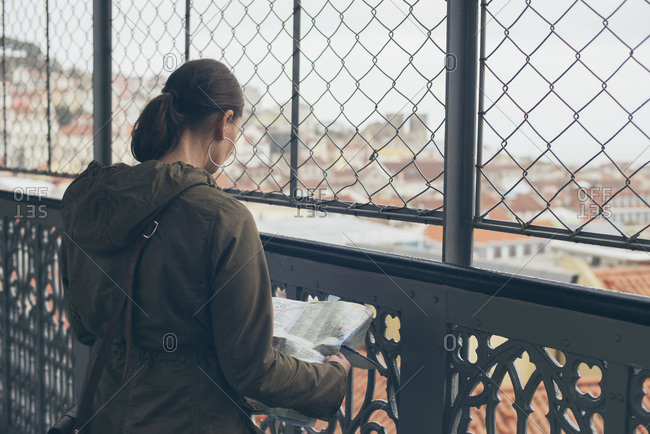 Woman reading a map on a bridge overlooking the city, Lisbon, Portugal