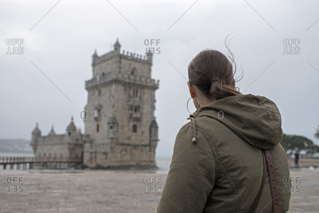 Woman looking at tower on a stormy day in Lisbon, Portugal