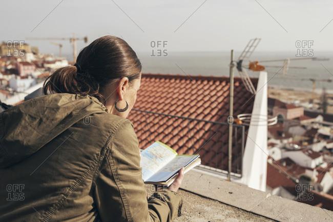 Tourist reading a book at viewpoint Santa Luzia in Lisbon, Portugal