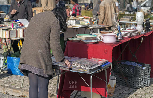 Woman looking at items in a second-hand market in Lisbon, Portugal