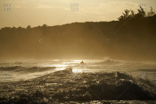 Silhouette of large rock in amongst crashing waves