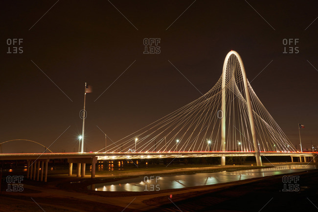 Bridge with tall arch illuminated at night