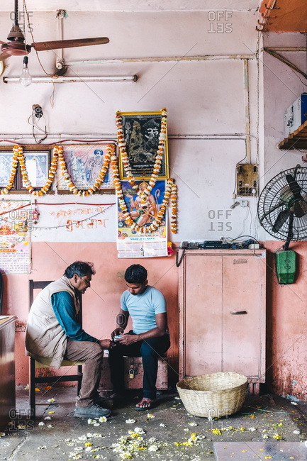 New Delhi, India - March 5, 2014: Two men in flower garland shop work on finances with calculator