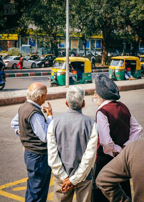 New Delhi, India - March 12, 2012: Back view of three men talking on street in New Delhi, India