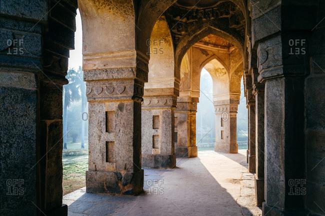 Sunlight shining through columns of building at Lodhi Gardens, New Delhi, India