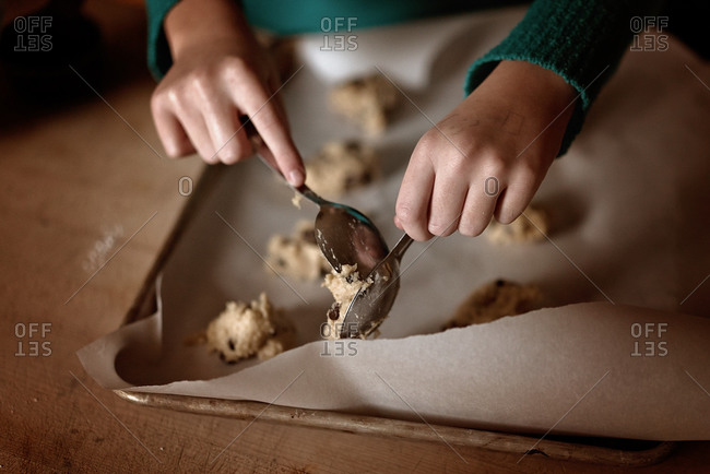 Hands of a girl putting spoonful of cookie dough on a baking sheet
