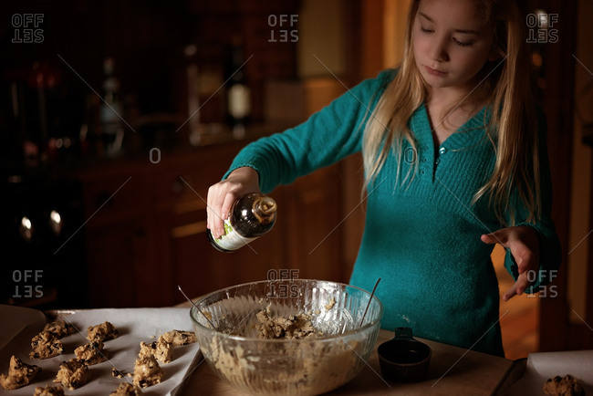 Girl pouring vanilla into a bowl of cookie dough