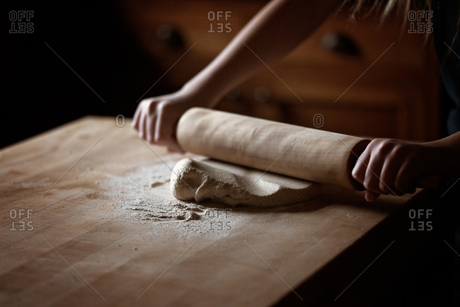 Girl rolling cookie dough with a rolling pin