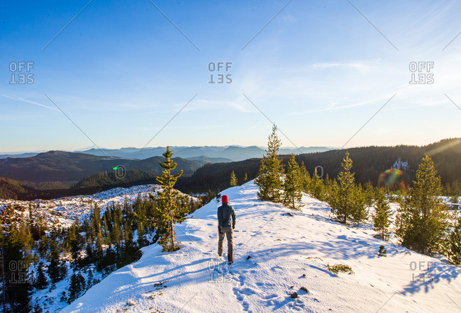 A hiker walking on a snowy ridge on Mount St. Helens, Washington