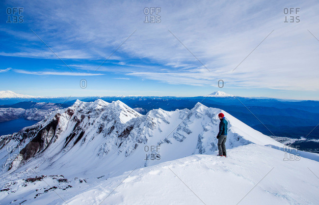Climber on the snowy summit of Mount St. Helens on a clear day in the Cascades of Washington