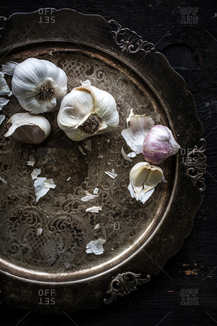 Garlic bulbs and cloves on antique platter