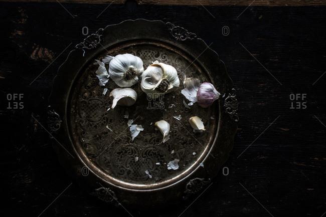 Garlic on antique platter on dark wooden table