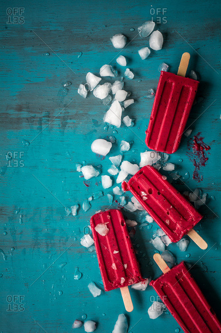 Red popsicles with ice on blue table