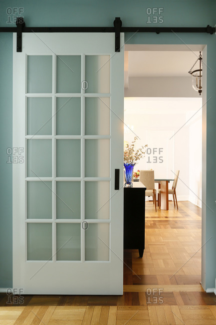 Apartment With Sliding Door On Track Leading To Dining Room Stock Photo