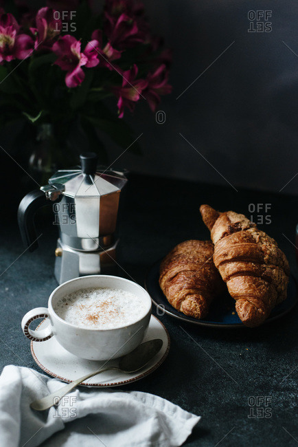 Cup of cappuccino, espresso pot and croissants