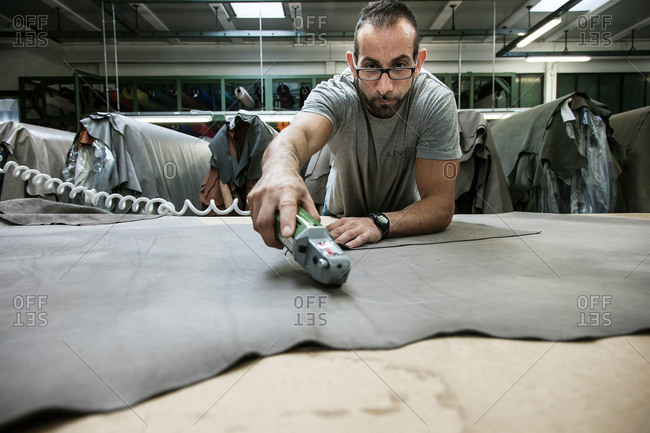 Anzano del Parco, Como, Italy - September 17, 2015: Man cutting leather piece for furniture