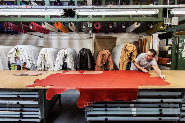 Anzano del Parco, Como, Italy - September 17, 2015: Man laying out leather in factory