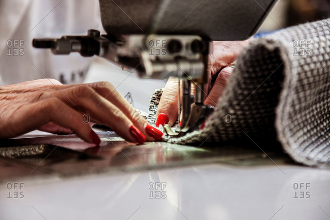 Hands sewing furniture fabric