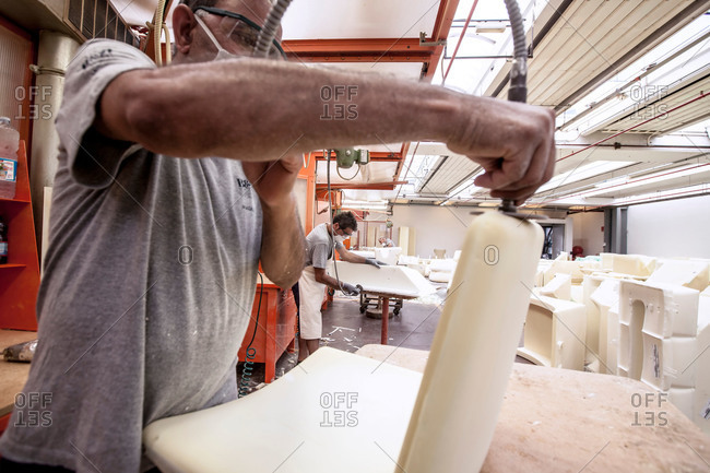 Novedrate, Como, Italy - July 20, 2015: Man shaping a furniture form