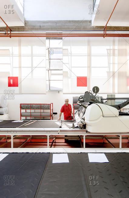 Meda, Brianza, Italy - July 21, 2015: Man at a fabric machine
