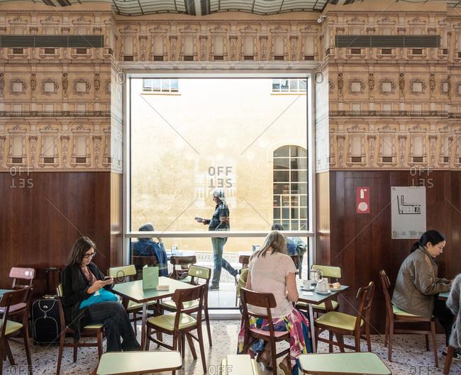Milan, Italy - October 8, 2015: Patrons in art gallery cafe, Milan