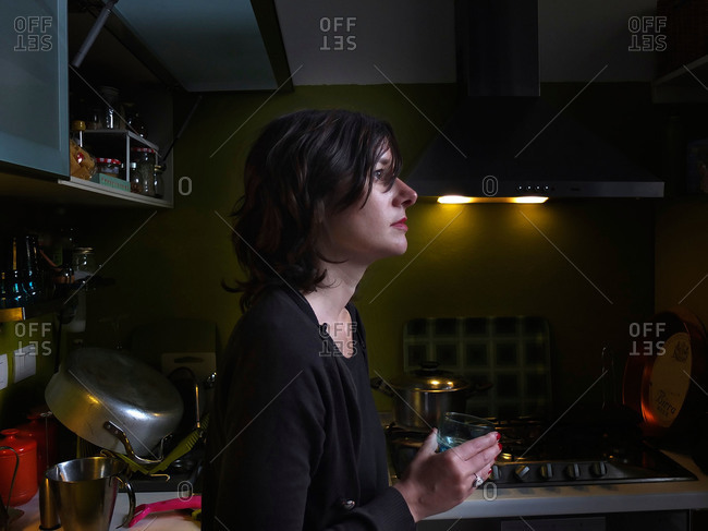 Woman holding a glass in kitchen