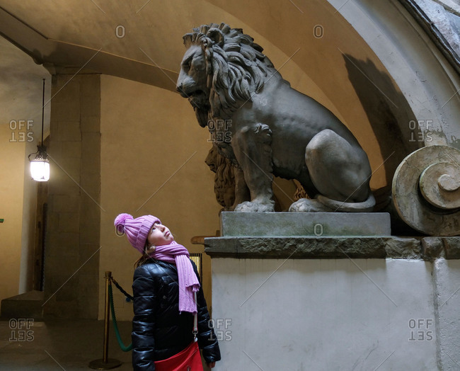 Girl looking at lion statue