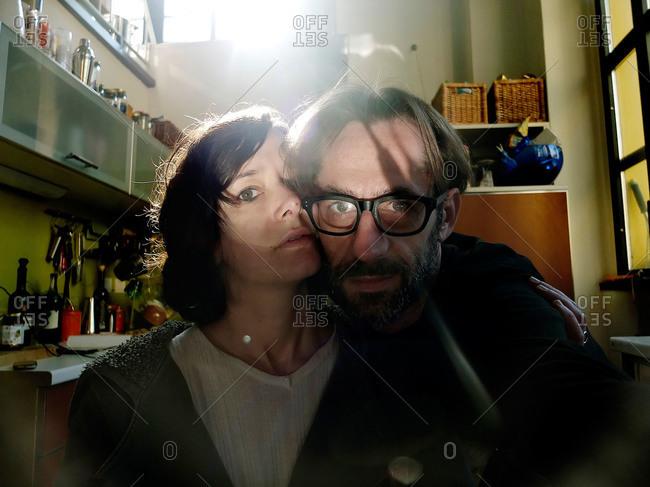 Portrait of sunlit couple in kitchen