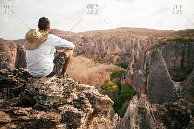 Man seated at mountain overlook, Serra da Capivara National Park, Brazil