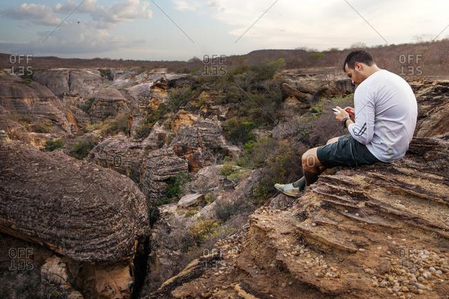 Man on phone at mountain overlook, Serra da Capivara National Park, Brazil
