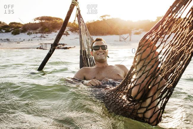 Man on hammock in ocean